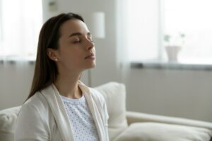 Calm serene woman resting sitting on couch in modern living room closed her eyes breath fresh humidified air. Fatigue relief repose, boost inner balance and mindfulness, meditation practice concept