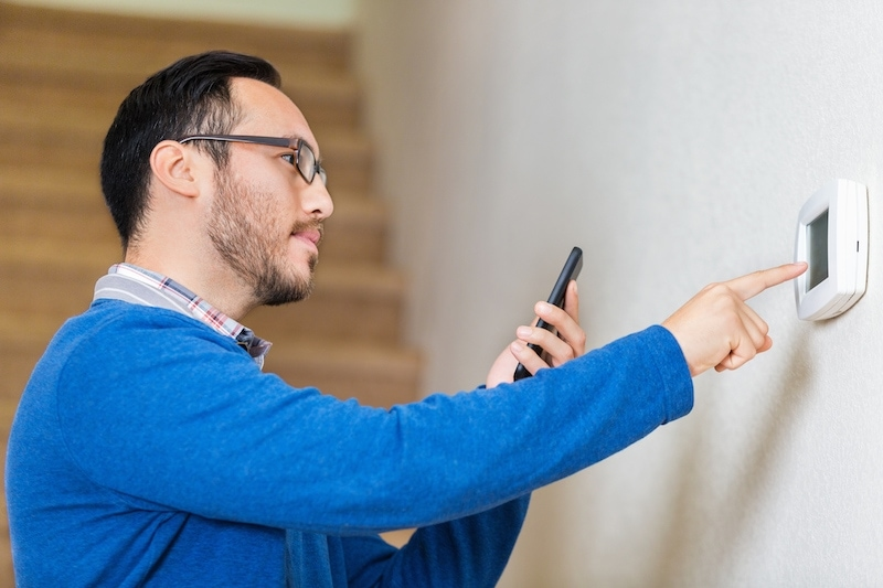 Mid adult hispanic man looks at smart phone for instruction as he learns to use thermostat in his new home. He is touching the digital termostat with his finger. He is standing in front of the stairs leading to the second floor of his home. He is wearing a blue sweater and glasses and has brown hair and a beard.
