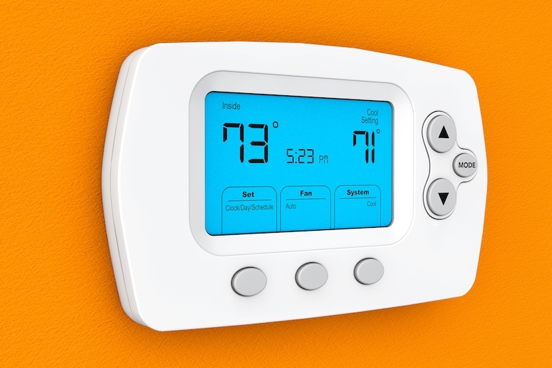 Modern Programming Thermostat on a orange wall in St. Louis, MO.