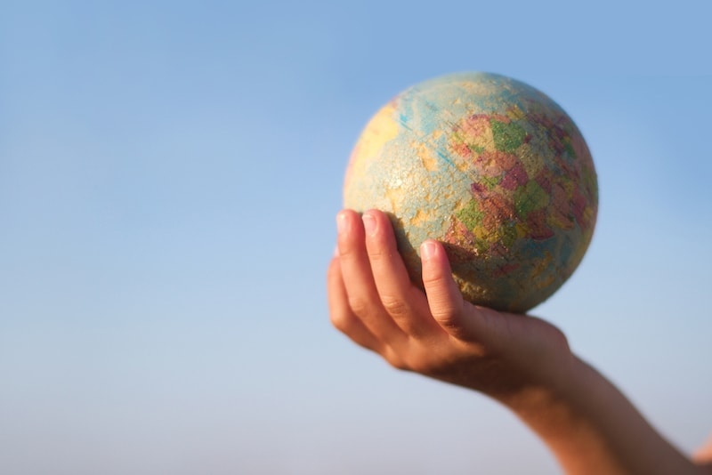 Front view of a child hand holding a damaged toy globe against a blue sky, shallow depth of field